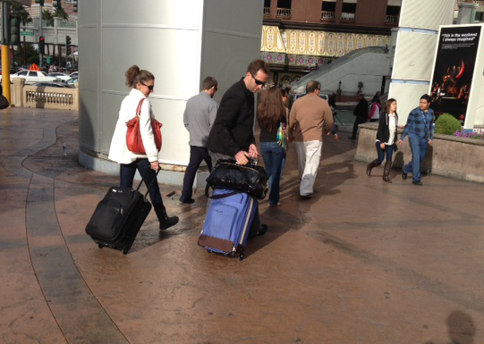 Travelers to Las Vegas who could have used Bags VIP luggage delivery service pulling roller bags down the Strip instead